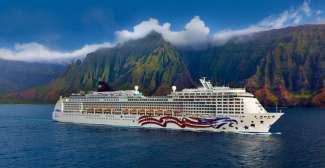 Ein Kreuzfahrtschiff der NCL Flotte, im Hintergrund die traumhafte Landschaft von Hawaii.